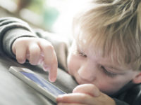 Little boy playing on a smart phone
