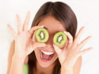 Woman holding kiwis up to her eyes